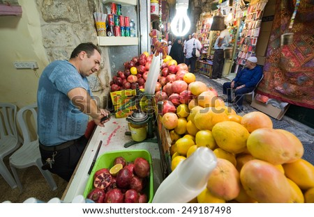 JERUSALEM, ISRAEL - OCTOBER 07, 2014: A man is making juice from a pomegranate in one of the small streets in the old city of Jerusalem