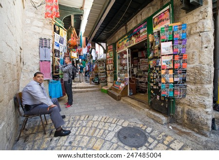 JERUSALEM, ISRAEL - OCTOBER 07, 2014: A man is sitting outside his shop on the Via Dolorosa, one of the small streets in the old city of Jerusalem - stock photo