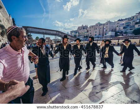 Jerusalem, Israel - October 22, 2015. Group of Orthodox Jews dance  next to ancient limestone wall known as Wailing Wall in the Old City of Jerusalem