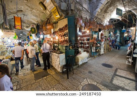 JERUSALEM, ISRAEL - OCTOBER 07, 2014: People are walking between the shops in one of the small streets in the old city of Jerusalem - stock photo
