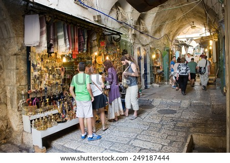 JERUSALEM, ISRAEL - OCTOBER 07, 2014: People are watching at souvenirs in one of the shops of the small streets in the old city of Jerusalem - stock photo