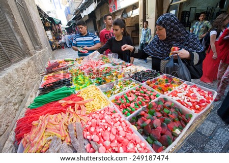 JERUSALEM, ISRAEL - OCTOBER 07, 2014: Woman are watching and buying sweets at a candy store in one of the small streets in the old city of Jerusalem - stock photo