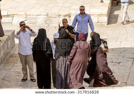 JERUSALEM, ISRAEL - SEP 22, 2014: Jews protected by security officers are walking on the temple-square and want to pray, this is the reason of the violence with muslims , September 22, 2014 in Israel - stock photo