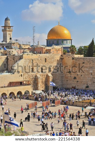 JERUSALEM, ISRAEL - SEPTEMBER 20, 2013:  Prayer at the Kotel. Religious Jews in white prayer shawls are going to pray at the Western Wall of the Temple. Sunny morning in the holiday of Sukkot
