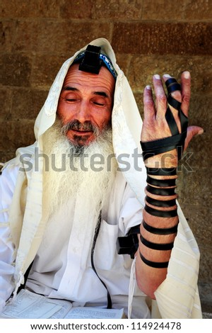 JERUSALEM-JULY 30: An old Jewish orthodox man begging for Tzedakah on July 30 2009 in Jerusalem, Israel.It is a Jewish religious obligation, which must be performed regardless of financial standing. - stock photo