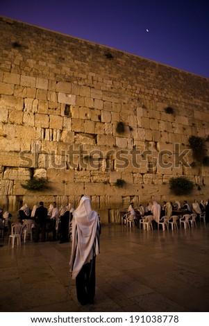 JERUSALEM - JUNE 26: Orthodox Jewish men pray at the famous wailing wall for Shabbas on June 261, 2011 in Jerusalem. - stock photo