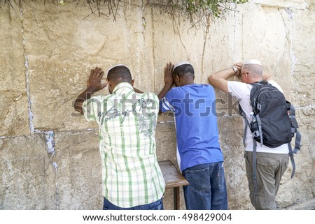 JERUSALEM - JUNE 3: The wailing Wall main religious symbol of Israel. Three jews praying at the wailing wall in the threshold of the holiday Lag ba-Omer on June 3, 2016 in Jerusalem.