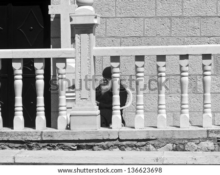 JERUSALEM - MARCH 29: An Armenian Orthodox priest sitting and resting in front of Tomb of the Virgin Mary Church. March 29, 2013 in Jerusalem, Israel.