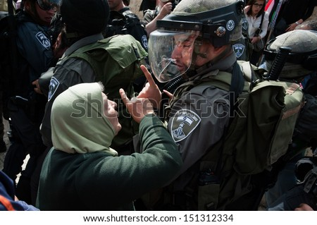 JERUSALEM - MAY 15: A Palestinian woman confronts Israeli police during clashes on Nakba Day at Damascus Gate, East Jerusalem, May 15, 2013.  - stock photo