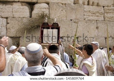 JERUSALEM-OCT 02: The Jews in prayer at the Western Wall during Jewish holiday of Sukkot, October 2, 2012 in Jerusalem, Israel.Etrog and Lulav is two of four species used during of Sukkot - stock photo