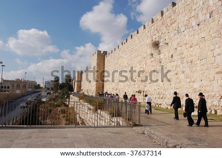 JERUSALEM - OCTOBER 9: Crowd walk at mid day near one of the ancient walls during Jewish holiday of Sukkot October 9, 2006 in Jerusalem, Israel.