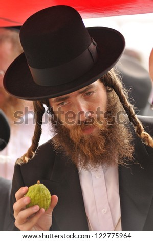 JERUSALEM - OCTOBER 1 : Jewish ultra-orthodox man inspect Etrogs at a four species market for the Jewish holiday of Sukkot on October 1 2012 in Jerusalem Mahne Yehuda Market ,Israel.