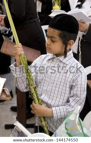 JERUSALEM -OCTOBER 02: Unidentified boy at the Western Wall during Jewish holiday of Sukkot October 02, 2012 in Jerusalem, Israel. Etrog and Lulav is two of four species used during of Sukkot. - stock photo