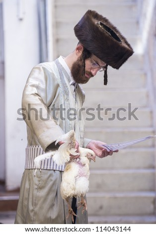JERUSALEM - SEP 25 : An ultra Orthodox Jewish man prays with a chicken during the Kaparot ceremony held in Jerusalem Israel in September 25, 2012 - stock photo