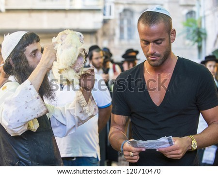 JERUSALEM - SEP 25 : An ultra Orthodox Jewish man waves a chicken over other man during the Kaparot ceremony held in Jerusalem Israel in September 25 2012 - stock photo