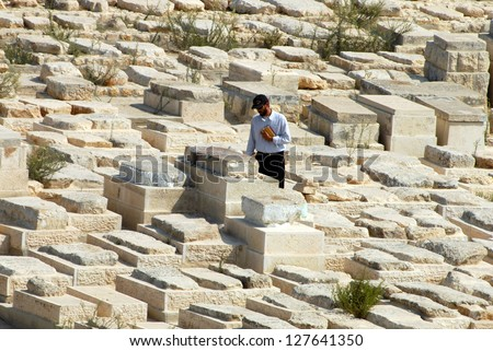 JERUSALEM - SEP 28:Jewish man visit a grave on Mount of Olives on September 28 2007 in Jerusalem ,Israel.  The Jewish cemetery on Mt olives is over 3,000 years and holds approximately 150,000 graves. - stock photo
