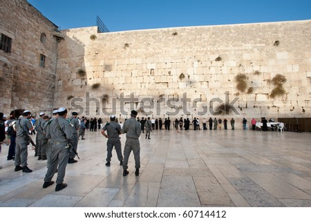 JERUSALEM - SEPTEMBER 7: Israeli security forces armed with assault rifles pray at the Western Wall in Jerusalem on September 7, 2010. Status of such holy sites is a major issue in peace negotiations. - stock photo