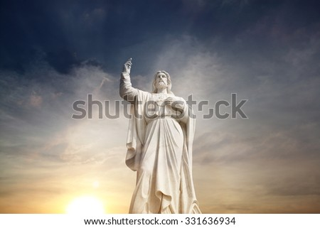 Jesus Christ against a surreal golden sunset. - stock photo