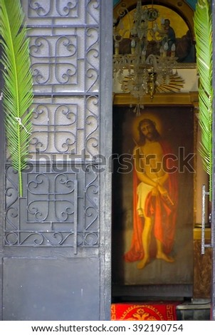 Jesus Christ behind the front church door The full length icon of Jesus Christ as it appears behind the front door of a Greek-Orthodox church  - stock photo