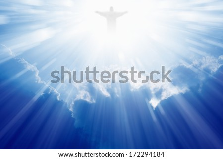 Jesus Christ in blue sky with clouds, bright light from heaven - stock photo