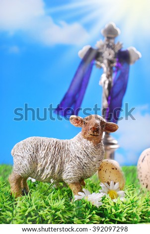 Jesus Christ on the cross and lamb figurine against blue sky as symbol of easter  - stock photo