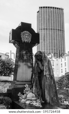 Jesus Christ on the cross, mourning Madonna statue on the grave of soldier at  Montparnasse Cemetery in Paris (France) and Montparnasse tower at background. Aged photo. Black and white. - stock photo