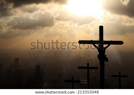 Jesus Christ on the cross on sunset background. - stock photo