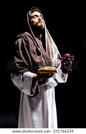 Jesus Christ praying to God consecration the bread and grapes in the dark black night - stock photo