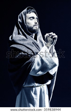 Jesus Christ praying to God with open arms in the dark black night - stock photo
