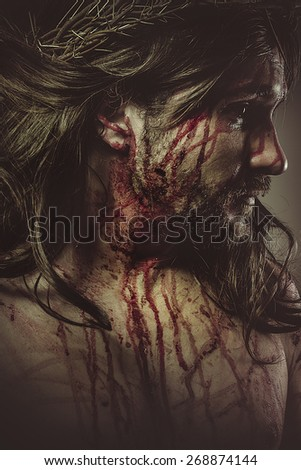 Jesus Christ with crown of thorns and blood on his face - stock photo