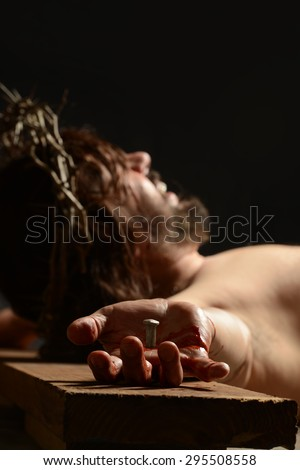 Jesus during the crucifixion with focus on his hand isolated on a dark background - stock photo