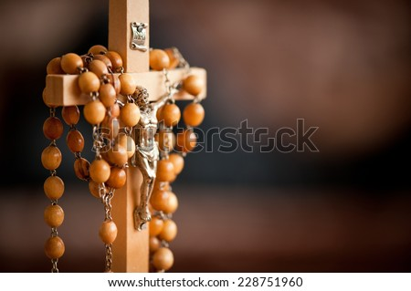 Jesus figurine and rosary made of wood beads dangle on wooden cross, INRI sign above, horizontal orientation, nobody. - stock photo