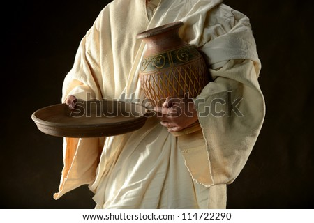 Jesus holding a jug and a pan against a dark background - stock photo