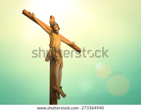 Jesus on the cross over blue sky background. (Public wooden Jesus on the cross) - stock photo