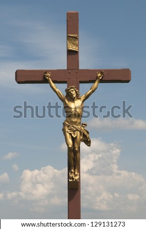 Jesus on the cross with clouds and blue sky in the background
