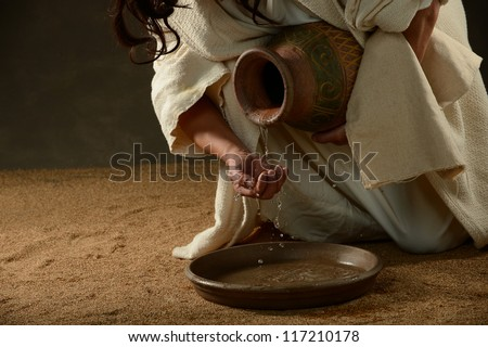 Jesus pouring water from a jug - stock photo