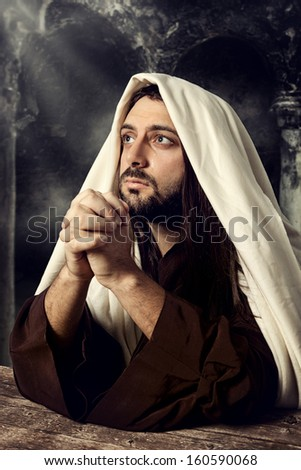 Jesus praying and looking up to heaven while he cries. - stock photo