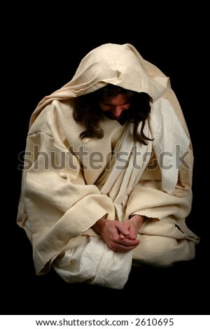 Jesus praying on his knees over a black background - stock photo