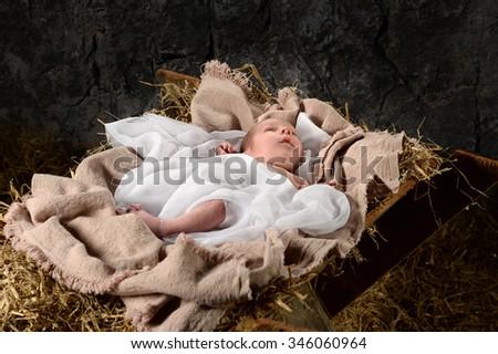 Jesus resting on manger in old barn - stock photo