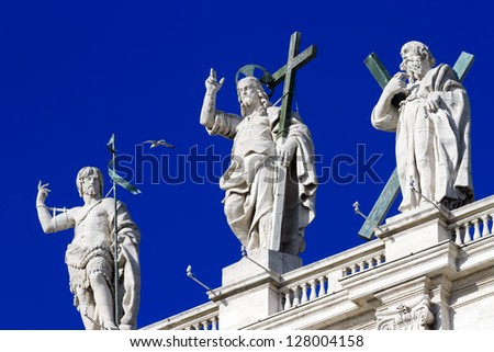 Jesus sculptures and sacred, standing on a roof of the Papal Basilica of Saint Peter, Vatican, against the blue sky - stock photo