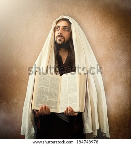 Jesus shows the holy bible on old beige background - stock photo