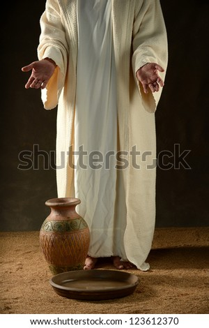 Jesus standing with a jar of water and a bowl - stock photo
