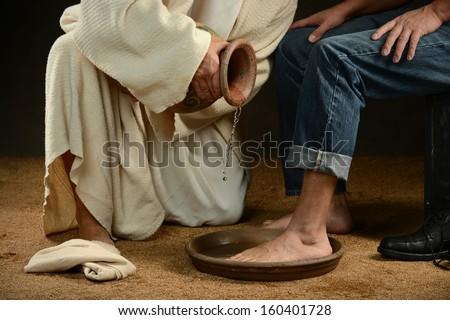 Jesus washing feet of modern man wearing jeans - stock photo