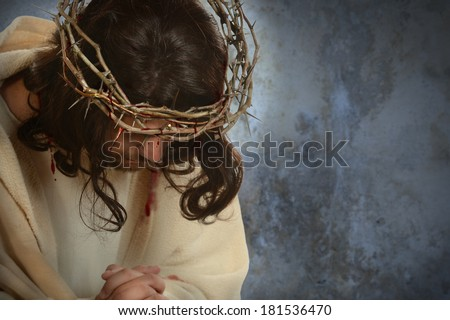 Jesus with crown of thorns with head down over old wall - stock photo