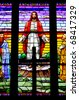 Jesus with his arms spread out on a stained glass window. - stock photo