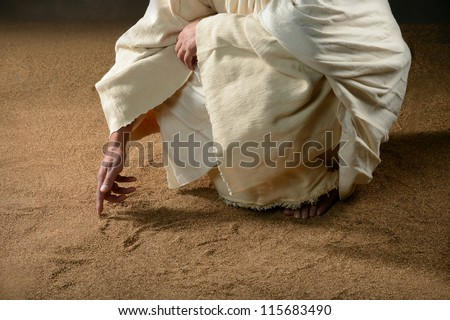 Jesus writing in the sand with finger - stock photo