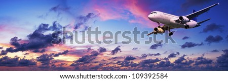 Jet aircraft is maneuvering for landing in a spectacular sunset sky. Panoramic composition. - stock photo