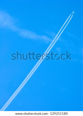 Jet airplane soars into the blue sky leaving contrails in its wake