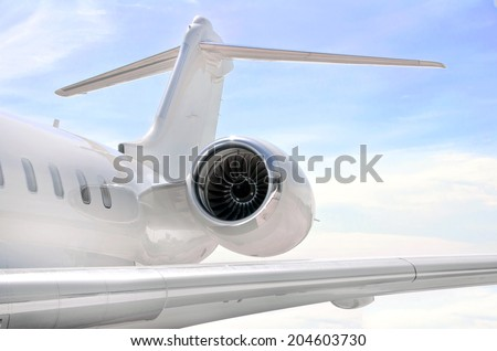 Jet Engine closeup on a modern private jet airplane with a tail wing - stock photo