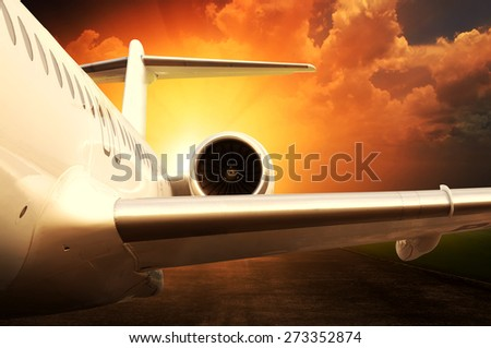 Jet engine on parked airplane over sunset background - stock photo